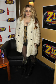 At the Z100 concert Kesha showed off her funky style in a short dress and a fur coat. She completed her look with a pair of knee high combat boots.