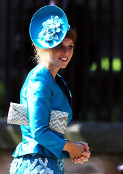 Famous for her statement hat at the Middleton wedding, Princess Beatrice wore another dramatic head piece at Zara Phillips' wedding. The blue dish cap featured a floral center piece and was paired with an iridescent jacket and textured skirt.