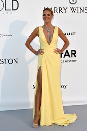 Heidi Klum looked sensational at the amfAR Cinema Against AIDS Gala in a yellow Atelier Versace gown that showcased both cleavage and leg.