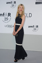 We love us some Clemence Poesy and this beautiful French girl can do no wrong in our eyes. After her last two summery outfits earlier in the week, Clemence decided to go for a darker look with this navy Chanel gown. White lace detailing kept the dress from feeling too heavy for the South of France locale, while red lips added just the right touch of seduction.