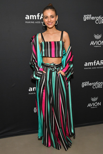 Victoria Justice looked striking in striped palazzo pants and a matching crop-top by Victoria Hayes at the amfAR GenCure Solstice 2018.