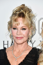 Melanie Griffith piled her hair on top of her head with messy-glam results for the amfAR Gala in Los Angeles.