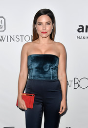 Sophia Bush accessorized with a red suede clutch that made a striking contrast to her teal jumpsuit at the amfAR Gala in Los Angeles.