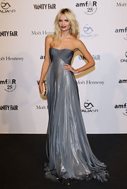 Natasha Poly shined at the amfAR soiree in Milan in a strapless gray dress with a draped bodice and a shimmering skirt. She paired the look with a burgundy pout.