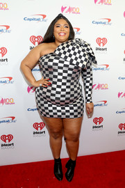 Lizzo hit the iHeartRadio Z100 Jingle Ball red carpet wearing a one-shoulder checkered mini dress.
