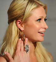 Paris Hilton paired her vibrant jumpsuit with a bold crystal cocktail ring. She finished off the look with full lashes and blonde tresses.