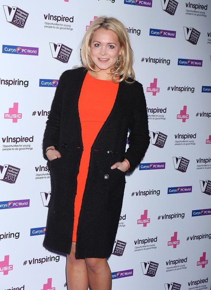 Poppy Jamie chose a basic black wool coat to pair over her vibrant orange dress at the vInspired Awards.