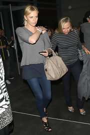 Charlize Theron went to a Lakers game in LA wearing a pair of black leather sandals.