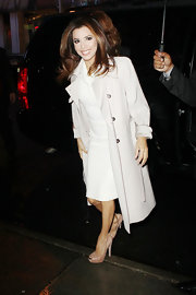 Eva Longoria topped off her chic white structural dress with nude peep-toe pumps.