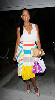 Garcelle Beauvais balanced the bold striped dress she wore to the Lia Sophia Launch with neutral accessories, including a woven nude envelope clutch.