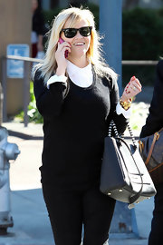 Reese looked charming in this basic black sweater she layered over her white button-down.