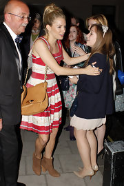 Sienna Miller teamed her flirty red-and-white dress with a tan leather Edna bag with a gold chain strap.