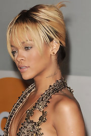 Rihanna attended the 2012 BRIT Awards wearing her hair in a classic French twist with long wispy bangs.