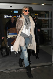 Adriana Karembeu swept through the airport in glam fashion, wearing a long shearling coat with a leopard scarf and purposely distressed jeans.