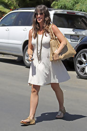 Alanis showed off her summer flair by pairing her white day dress with a layered gold necklace.