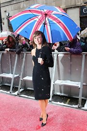Amanda Holden stayed cheerful in the London rain under a bold Union Jack umbrella.