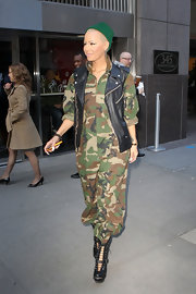 Amber Rose further toughened her camo jumpsuit with a leather biker vest and lace-up boots.