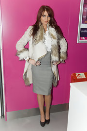 Amy wears a large fur-adorned leather coat at the Sally Salon in London.