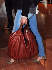 Asia Argento was spotted at Nice Airport carrying a chic rusty red leather tote.