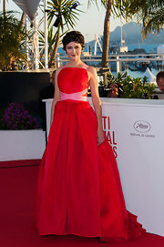 Audrey Tautou stunned in a red ball gown that was accented with a pink sash and matching pink straps.