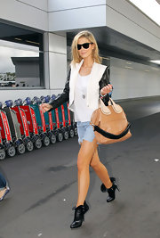 Delta Goodrem arrived on a flight at Sydney Airport wearing an ultra-chic pair of ankle boots.