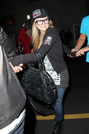 Avril kept it casual while hitting the club with her new boy toy. The singer sported jeans with a hoodie and a printed trucker cap.