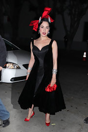 Dita Von Teese attended Perez Hilton's birthday party wearing a pair of ruby red satin pumps to match her stunning hat and handbag.