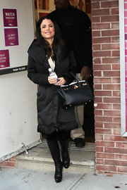 Bethenny Frankel bundled up for the cold weather in a black puffy coat paired with black leather knee-high boots.