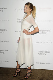 Lily Donaldson teamed her sheer white dress with black strappy spider web style sandals.
