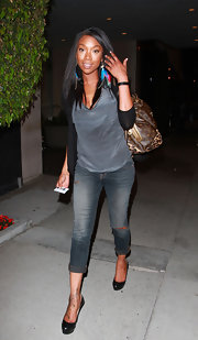 Brandy accessorized her casual denim look with a classic LV bag with leopard print accents.