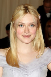 Dakota Fanning attended the Met Gala wearing 19th century enamel and diamond flower brooches worn in her hair.