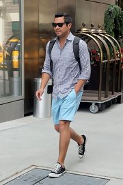 Cash Warren sported a summery get-up in NYC, consisting of pastel blue Bermuda shorts, a gingham button-down, and sneakers.