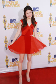Miranda Cosgorve paired her on-trend nude pumps with an orange frilly dress.