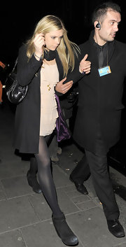 Chelsy Davy layered a minimalist black coat over a super short tiered blush dress.