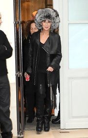 Cher went shopping in Paris looking glam in thigh-high black croc-embossed boots, a matching coat, and a fur hat.