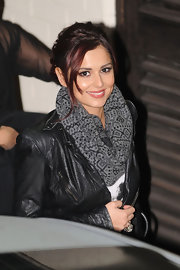 Cheryl dons this subtle gray patterned scarf with her leather jacket and pulled back hair.