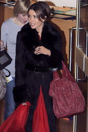 Dannie Minogue added a luxe touch to her evening outfit with a burgundy tote. The stud embellished tote matched the glam vibe of her fur-trimmed coat.