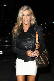Joanna Krupa paired her sleek leather jacket with a monogrammed printed canvas bag.