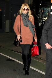 Claudia looks effortlessly stylish at the airport in a gray knit scarf and angora sweater.
