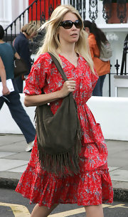 Claudia paired her printed day dress with a brown fringe hobo bag. The perfect accessory to add to her boho-glam look.