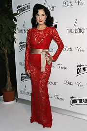 Dita Von Teese rocked a crimson lace gown with a nude satin bow to show off her hourglass figure.