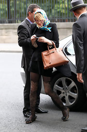 Courtney showed off her tan leather tote bag while arriving at her hotel in Paris.