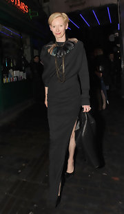 Tilda donned a dramatic floor length black gown with a hip-high slit and a feathered collar for Box Nightclub in London.