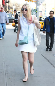 Dakota Fanning chose a sleeveless button down to pair with a mini skirt for her casual fun-in-the sun look.