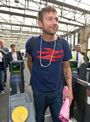 Damon Albarn wore a white beaded necklace when he touched down in Glasgow.