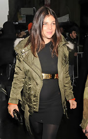 Julia Restoin-Roitfeld gave her tight black sweater dress an effortless feel with the addition of an olive down jacket with a fur-trimmed hood.