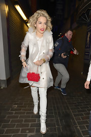Rita added some color to her all-white look with this hard case, plastic shoulder bag.