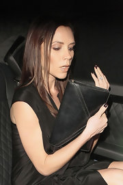 Victoria Beckham carried a sleek black leather envelope clutch during London Fashion Week.