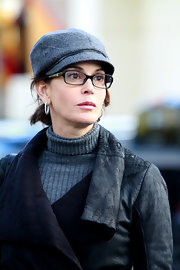 Teri wears a gray cap with her sophisticated black rimmed glasses.