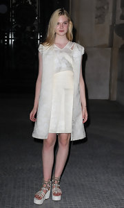 Elle Fanning complemented her ivory A-line dress with a pair of strappy white flatform sandals.